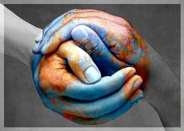 Fotografia de manos entrelazadas, formando una esfera pintada como la Tierra
