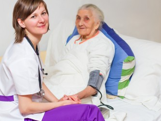 young nurse caregiving an old lady lying in bed