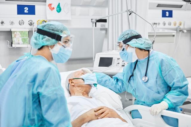 Profesionales sanitarios hablando con un paciente | iStock