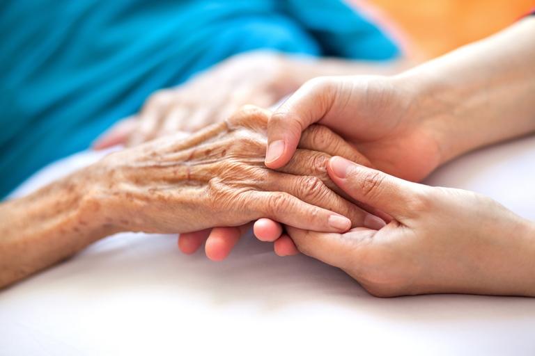 profesional sanitario dando la mano al paciente